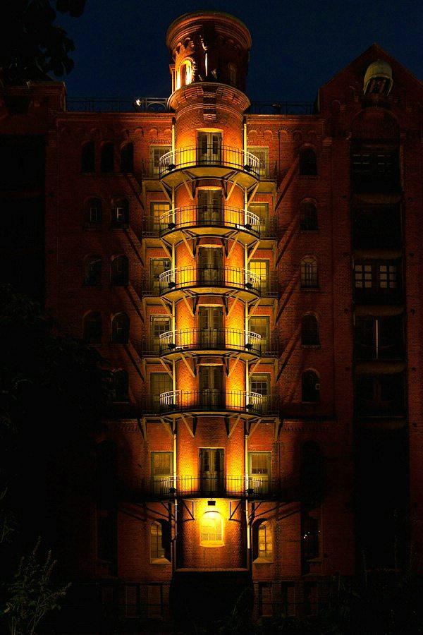 Foto eines beleuchteten Lagerhauses in der Speicherstadt in Hamburg.