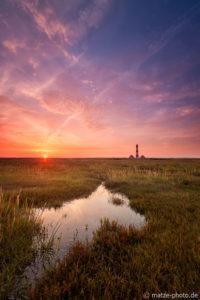 Der Leuchtturm Westerheversand bei Sonnenaufgang.